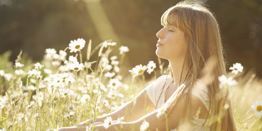 Woman+with+eyes+closed+sitting+in+meadow.