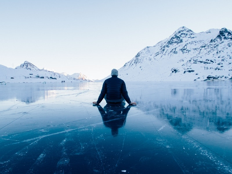 Man+sitting+on+frozen+water.