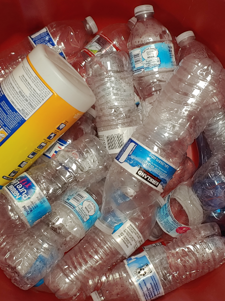 A recycle bin containing  many water bottles and one wet wipes container.