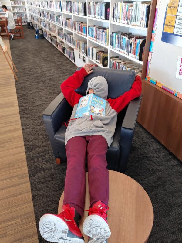 A teenager who fell asleep while reading Big Nate in a chair.