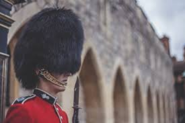 A Royal gaurd gaurding in the front of a castle