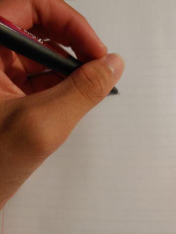 A person using a pencil with their left hand to write.
