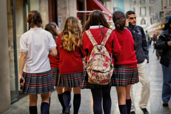 A group of students wearing uniforms  after another day of school.