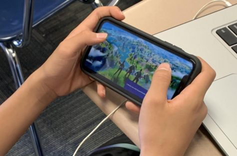 An addicted teenager glued to his screen playing the game Fortnite.