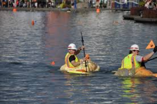 Two men in a pumpkin boat racing on a lake to the finish line.