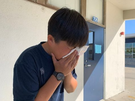 A student coughing from a sickness due to not having vaccines.