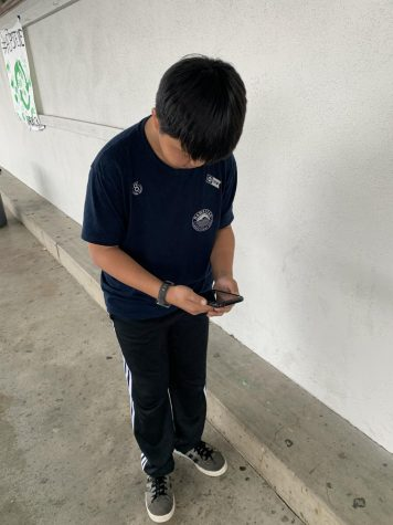 A child using his phone while walking on the streets.